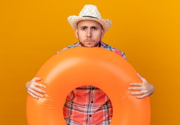 Ontevreden jonge reiziger man met stro strand hoed met zwemring geïsoleerd op oranje muur met kopie ruimte