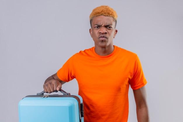 Ontevreden jonge reizigersjongen die de oranje koffer van de t-shirtholding met fronsend gezicht draagt dat zich over witte muur bevindt