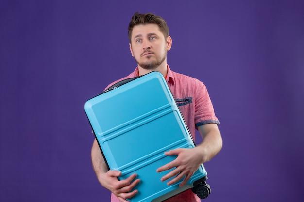 Ontevreden jonge reizigersmens die blauwe koffer houdt die met droevige uitdrukking opzij kijkt