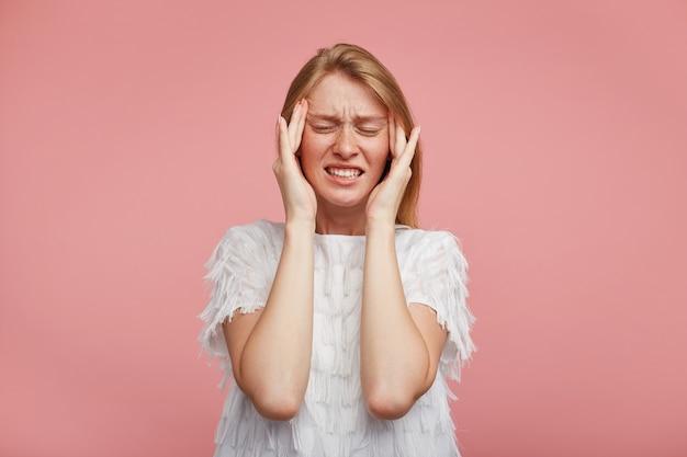 Ontevreden jonge roodharige dame met casual kapsel, haar gezicht met gesloten ogen fronsend fronsend en vingers op haar slapen te houden, geïsoleerd op roze achtergrond