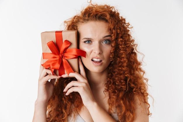 Ontevreden jonge roodharige krullende vrouw met verrassingsdoos cadeau.