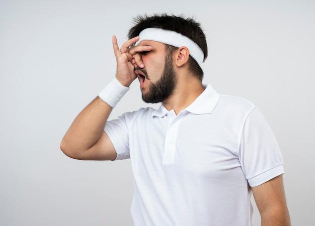 Ontevreden jonge sportieve man met hoofdband en polsband bedekt gezicht met hand geïsoleerd op een witte muur