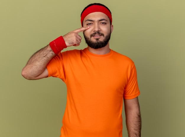 Ontevreden jonge sportieve man met hoofdband en polsbandje vinger op oog geïsoleerd op olijfgroene achtergrond