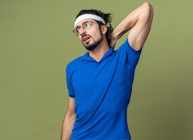 Ontevreden jonge sportieve man met hoofdband met polsbandje hand op nek zetten