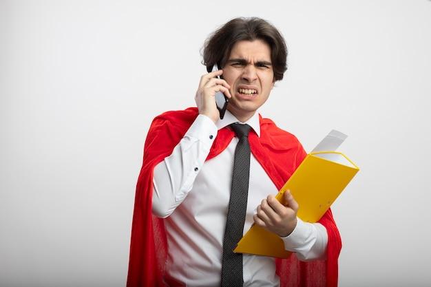 Ontevreden jonge superheld kerel die de map van de stropdasholding draagt en op telefoon spreekt die op wit wordt geïsoleerd