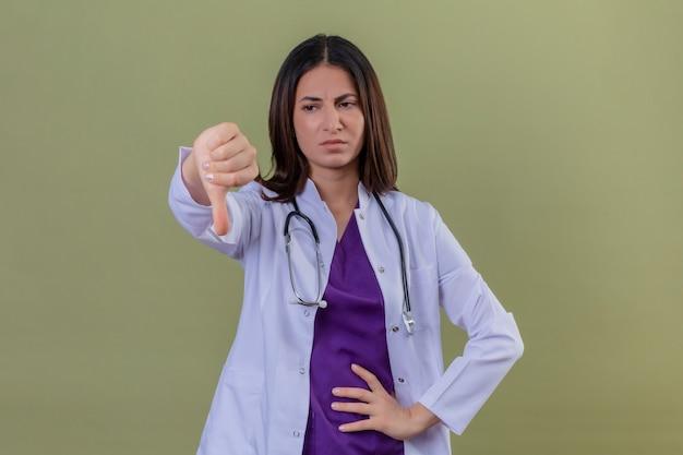 Ontevreden jonge vrouw arts die witte jas draagt en met een stethoscoop die duimen toont die neer op geïsoleerde groen staan