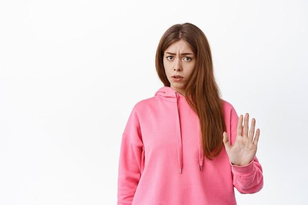 Ontevreden jonge vrouw die aanbod blokkeert, iets slechts weigert, stopblokgebaar toont, afwijst, over witte muur staat