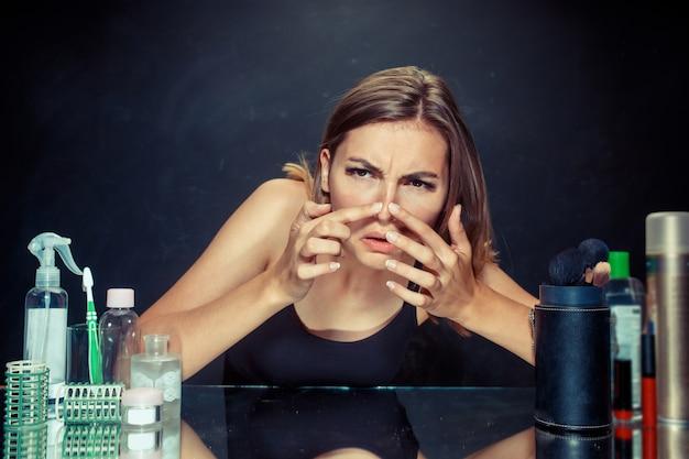 Ontevreden jonge vrouw die haar zelf in spiegel op zwarte muur bekijkt