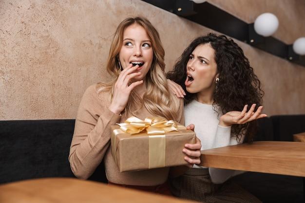 Ontevreden jonge vrouw die naar haar mooie vriendin kijkt die in café zit met de huidige geschenkdoos