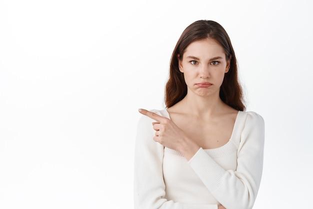 Ontevreden jonge vrouw die wijsvinger opzij wijst, slechte promo toont, mokkend van streek, teleurgesteld kijkt, tegen een witte muur staat