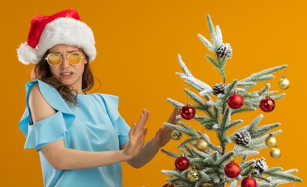 Ontevreden jonge vrouw in blauwe bovenkant en santahoed die gele glazen draagt