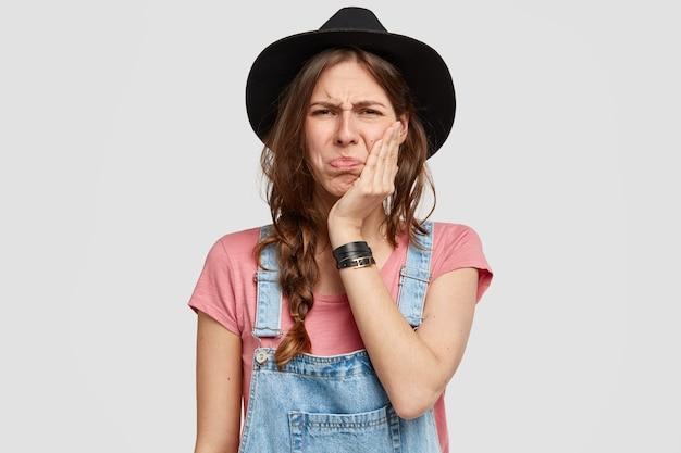 Ontevreden jonge vrouw landarbeider heeft een ellendige gezichtsuitdrukking, raakt de wang met de hand, gekleed in een denim overall en een modieuze hoed