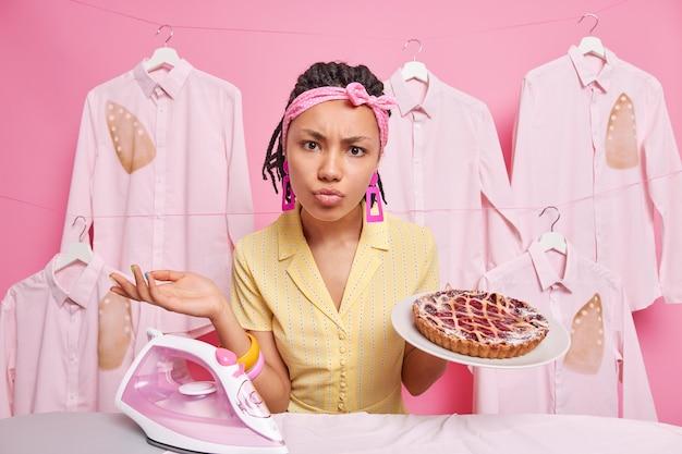 Ontevreden jonge vrouw met een donkere huid kijkt verbaasd naar de camera verhoogt de palm bakt heerlijke taartijzers wasserij thuis doet huishoudelijke klusjes. drukke huisvrouw heeft veel taken te doen