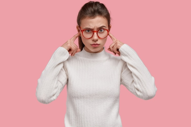 Ontevreden jonge vrouw stopt oren met wijsvingers, heeft geïrriteerde gezichtsuitdrukking, vermijdt negatief geluid, geïrriteerd door luide muziek