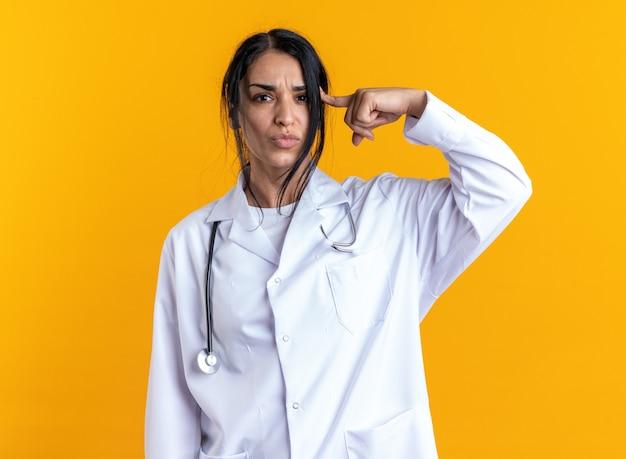 Ontevreden jonge vrouwelijke arts die een medisch gewaad draagt met een stethoscoop die de vinger op de tempel zet die op gele achtergrond wordt geïsoleerd