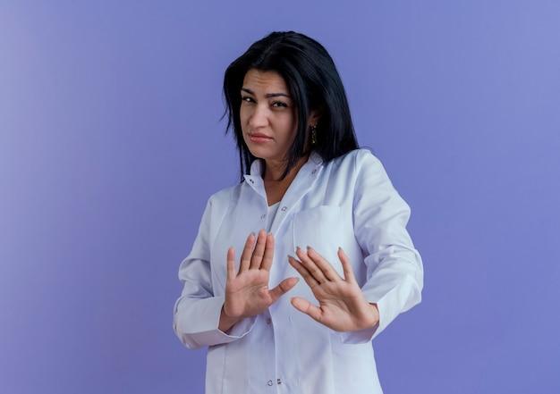 Ontevreden jonge vrouwelijke arts die medische mantel draagt die geen gebaar doet dat op purpere muur met exemplaarruimte wordt geïsoleerd