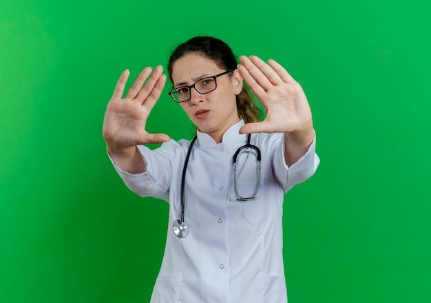 Ontevreden jonge vrouwelijke arts die medische mantel en stethoscoop en bril draagt die stopgebaar doet dat op groene muur met exemplaarruimte wordt geïsoleerd