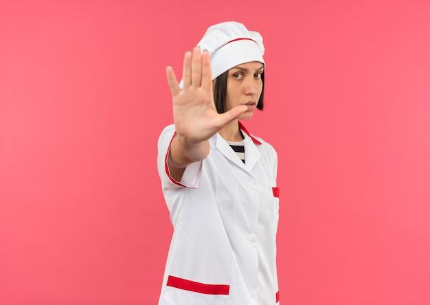 Ontevreden jonge vrouwelijke kok in chef-kok uniform gebaren stop bij camera geïsoleerd op roze achtergrond met kopie ruimte