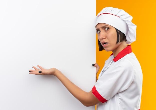 Ontevreden jonge vrouwelijke kok in eenvormige chef-kok die zich dichtbij bevindt en met hand wijst naar witte muur die op oranje achtergrond met exemplaarruimte wordt geïsoleerd