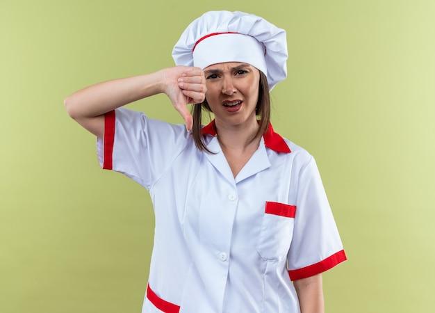 Ontevreden jonge vrouwelijke kok in uniform van de chef-kok met duim omlaag geïsoleerd op olijfgroene muur