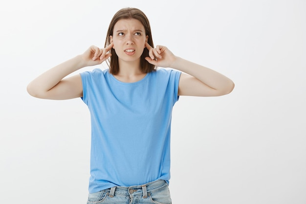 Ontevreden jonge vrouwelijke student die luide buren klaagt, oren dicht met vingers