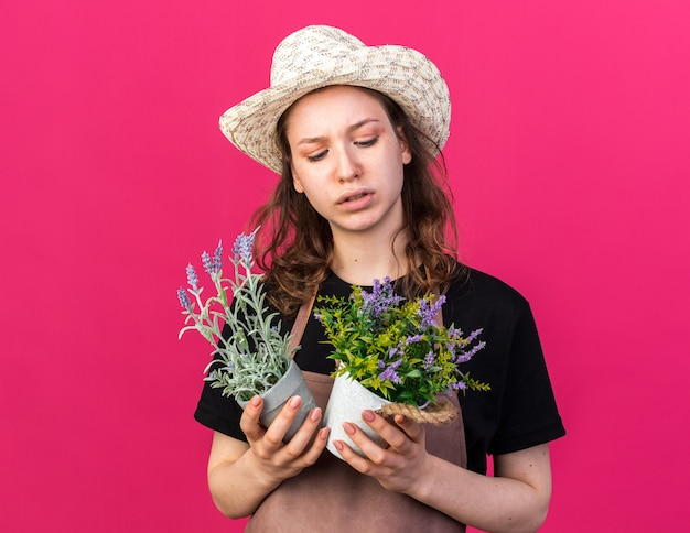 Ontevreden jonge vrouwelijke tuinman die een tuinhoed draagt en naar bloemen kijkt in bloempotten die op een roze muur zijn geïsoleerd