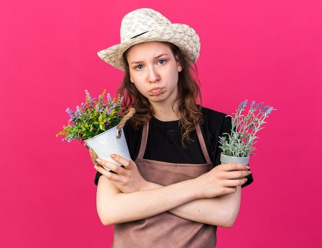 Ontevreden jonge vrouwelijke tuinman met een tuinhoed die bloemen vasthoudt en kruist in bloempotten geïsoleerd op roze muur