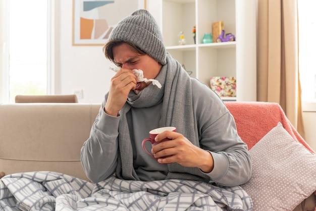 Ontevreden jonge zieke man met sjaal om nek met wintermuts veegt zijn neus af met tissues en houdt een kopje vast terwijl hij op de bank in de woonkamer zit