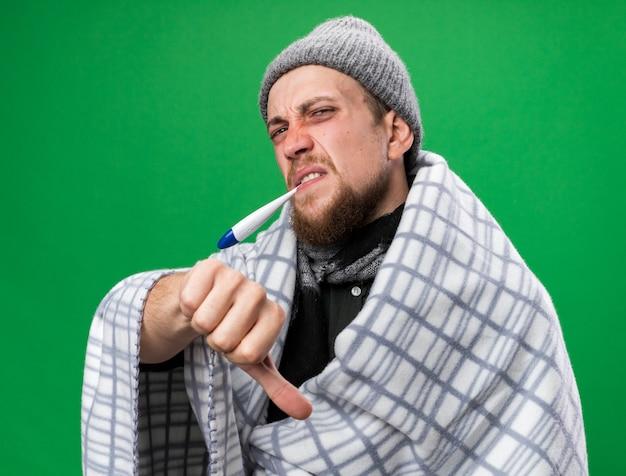 Ontevreden jonge zieke slavische man met sjaal om nek gewikkeld in plaid met winterhoed met thermometer in zijn mond duimen naar beneden