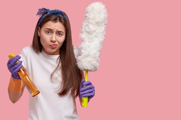 Ontevreden jongedame fronst gezicht van ontevredenheid, draagt een pot met afwasmiddel en borstel, draagt rubberen handschoenen, voelt zich het huishoudelijk werk beu