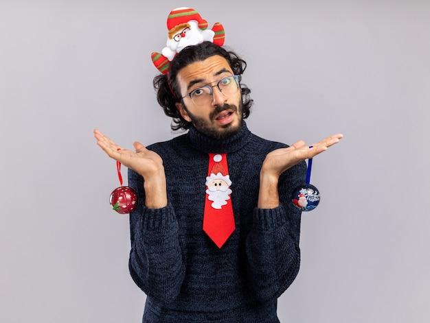 Ontevreden kantelend hoofd jonge knappe kerel die kerstmisband met haarring dragen die kerstmisballen houdt die op witte achtergrond worden geïsoleerd