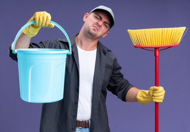 Ontevreden kantelend hoofd jonge knappe schoonmaakster die t-shirt en pet met glaven draagt ?? die emmer met dweil houdt geïsoleerd op paarse muur
