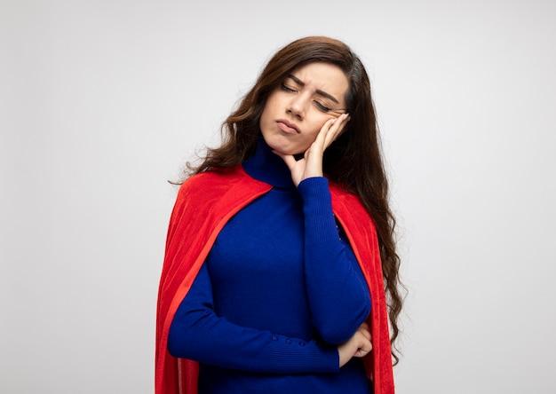Ontevreden kaukasisch superheldmeisje met rode cape legt hand op gezicht en staat met gesloten ogen