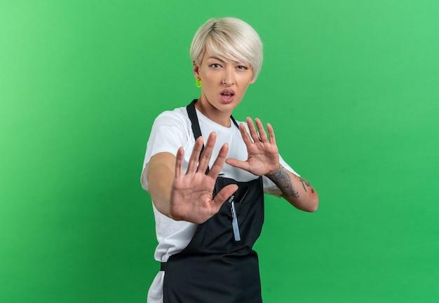 Ontevreden kijken naar camera jonge mooie vrouwelijke kapper in uniform weergegeven: stop gebaar geïsoleerd op groene achtergrond