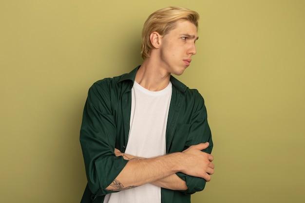 Ontevreden kijkend naar de jonge blonde kerel die aan de zijkant een groene t-shirt draagt die de handen kruist
