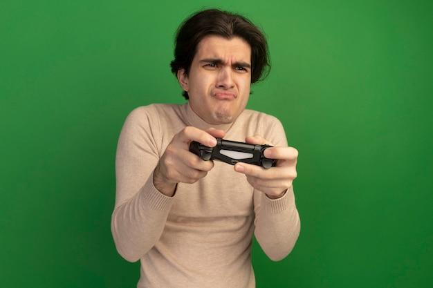 Ontevreden kijkend naar kant jonge knappe kerel met joystick van de spelbesturing die op groene muur wordt geïsoleerd