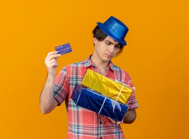 Ontevreden knappe blanke man met blauwe feestmuts houdt geschenkdozen en creditcard vast