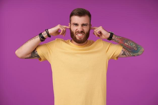 Ontevreden knappe jonge getatoeëerde man met baard die zijn voorhoofd fronst en wijsvingers in zijn oren steekt, in een poging vervelende geluiden te vermijden, geïsoleerd op paars