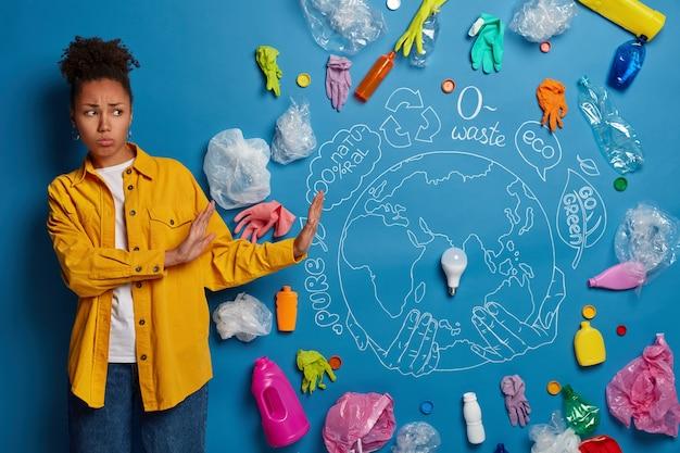Ontevreden krullende afro-amerikaanse vrouw maakt stopgebaar, ontkent het gebruik van plastic, kijkt verdrietig naar afval en afval, houdt zich bezig met het recyclen van afval, wil in een schone omgeving leven.