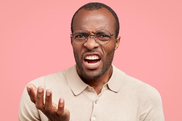 Ontevreden man fronst gezicht van ontevredenheid, voelt afkeer, toont tanden, staat binnen tegen roze muur, gekleed in beige t-shirt