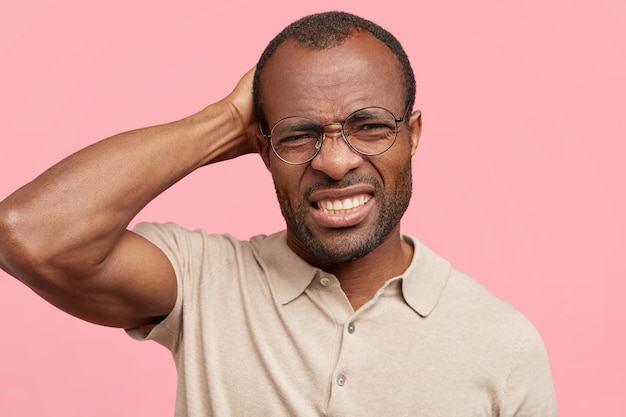 Ontevreden man fronst zijn wenkbrauwen, krabt op zijn hoofd en betreurt wat hij zei, draagt een beige t-shirt