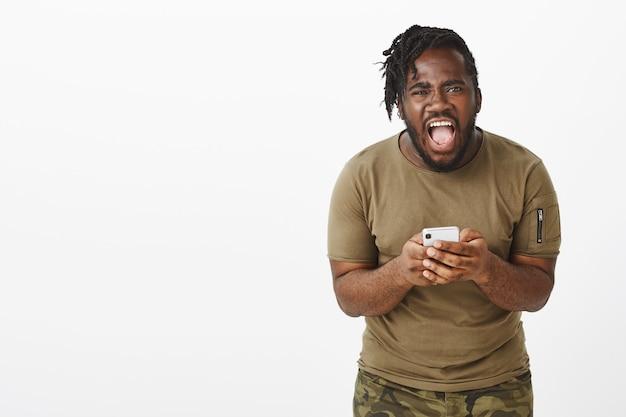Ontevreden man in een bruin t-shirt poseren tegen de witte muur met zijn telefoon