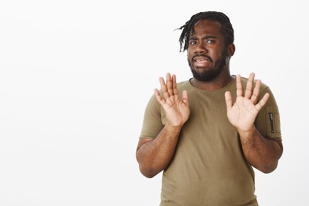 Ontevreden man in een bruin t-shirt poseren tegen de witte muur
