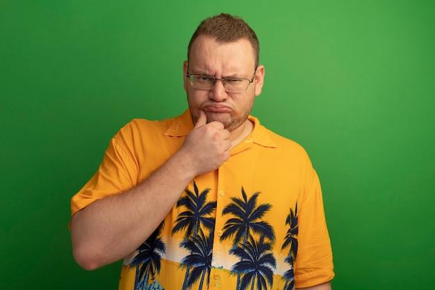 Ontevreden man in glazen en oranje overhemd fronsende wenkbrauwen die zich over groene muur bevinden