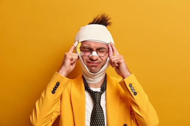 Ontevreden man lijdt aan ondraaglijke migraine na een verwonding, gekleed in formele kleding, heeft blauwe plekken en een gebroken neus, herstelt na een moeilijke operatie, geïsoleerd op gele muur