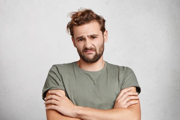 Ontevreden man met baard en snor fronst zijn wenkbrauwen, spreekt zijn aarzeling en bezorgdheid uit,