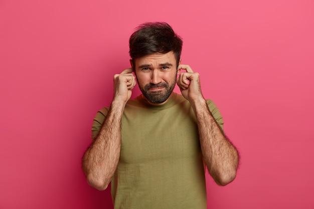 Ontevreden man met baard luistert niet naar het gesprek van vrienden, stopt oorgaatjes met vingers, kan zich niet concentreren in een lawaaierige atmosfeer, vermijdt onaangenaam geluid, gekleed in een casual t-shirt, poseert binnen