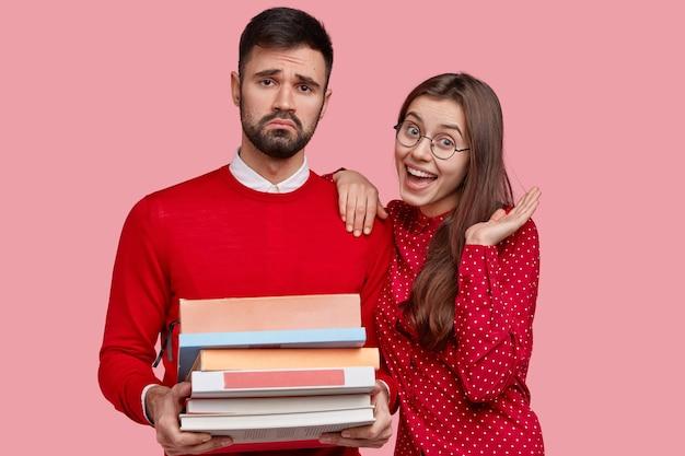 Ontevreden man met een boos blik, draagt stapel boeken, moe van het studeren, gelukkige blanke vriendin drukt goede emoties uit
