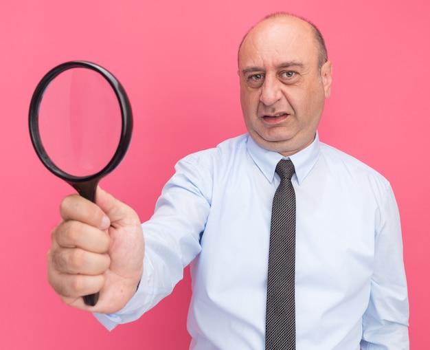 Ontevreden man van middelbare leeftijd met een wit t-shirt met stropdas die vergrootglas standhoudt dat op roze muur wordt geïsoleerd