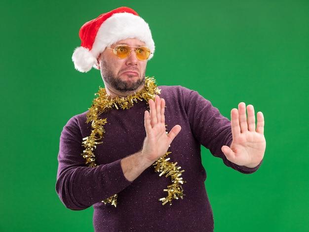 Ontevreden man van middelbare leeftijd met kerstmuts en klatergoud slinger rond nek met bril kijken kant doen weigering gebaar geïsoleerd op groene achtergrond